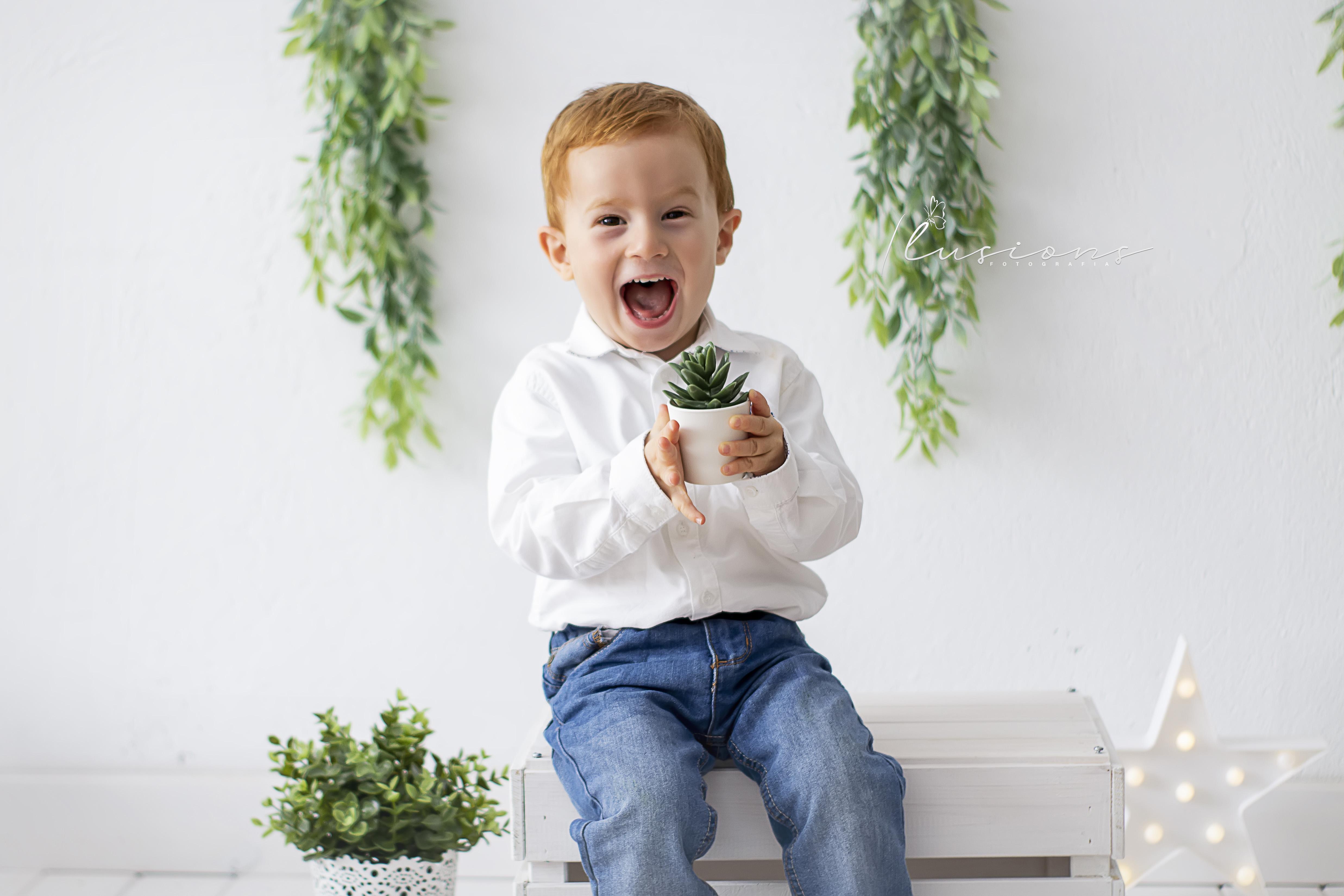 fotografia niño sonriente con planta