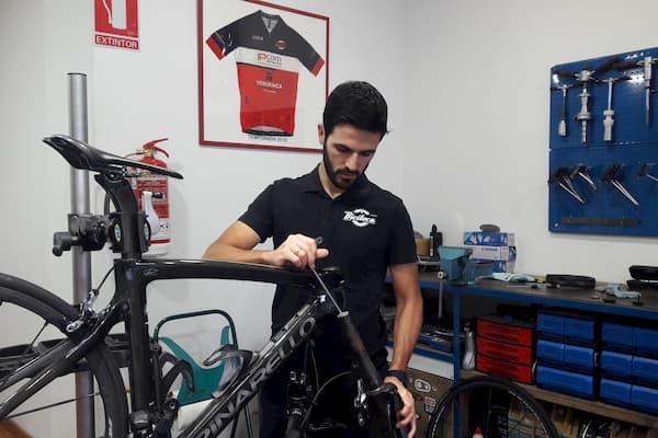 Hombre arreglando bicicleta.