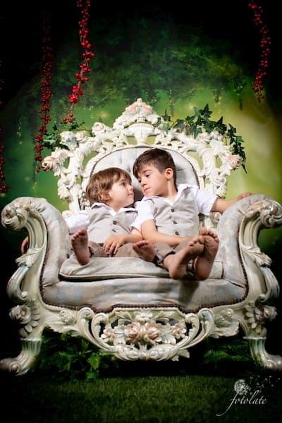 2 Niños sentados en silla.